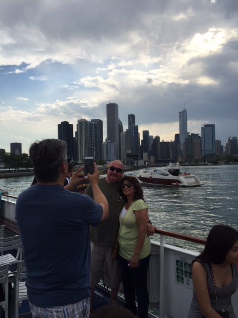 Honey taking a picture of Martha & Darrel with the skyline in the distance.